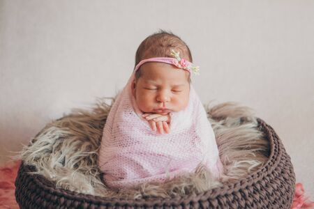 portrait of a sleeping newborn baby in a headband with flower. Health concept: IVF, baby accessories