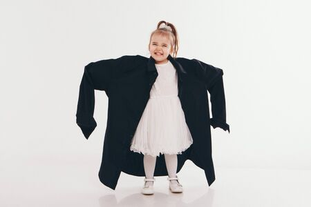 a little girl tries on dad's shirt. Child in big black clothes on white background. Concept of children's games, imitation of adult life, fashion