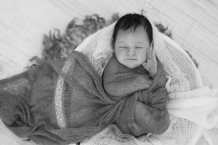 newborn baby wrapped in a blanket sleeping in a basket. concept of childhood, healthcare, IVF. Black and white photo Stok Fotoğraf - 134407915