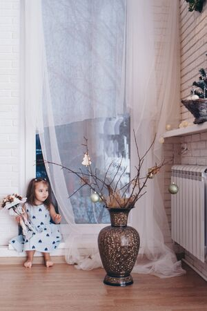the girl is sitting next to a vase of flowers and empty picture frames. Interior decoration concept, design Stok Fotoğraf