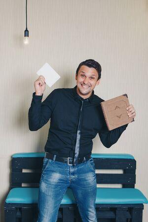 le gars tient une grande bannière, des livres. Le concept d'espace vide pour la publicité, des modèles pour la démonstration de textes