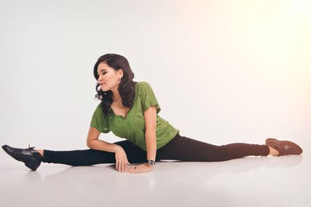 The woman sat down on the twine. classes in the fitness club. the girl is engaged in recreational gymnastics. sports exercises and stretching: athletics