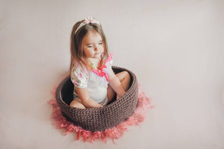 girl sitting in a basket. concept of childhood, health care, IVF Stok Fotoğraf - 134408091