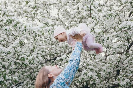 man holding child. March 8: man and girl among flowers. Baby in fly. the concept of congratulations, women's holidays, natural make up