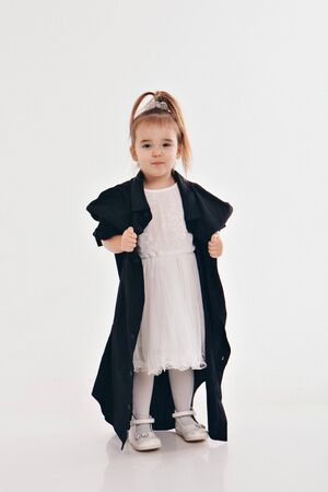 a little girl tries on dads shirt. Child in big black clothes on white background. Concept of childrens games, imitation of adult life, fashion