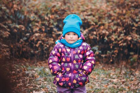 a small child with mother in a warm suit walks in the woods. autumn park. The concept of childrens fashion, accessories, outdoor walks Stok Fotoğraf