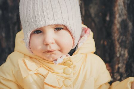 a little girl in a warm hat on his head smiled. the concept of childhood, health, IVF, cold time Stok Fotoğraf - 134408120