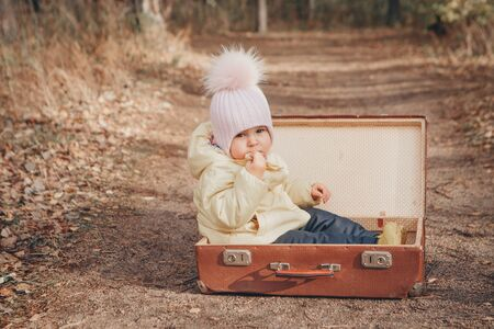 a small child in a warm suit sits in a suitcase on the road. The concept of the change of residence, move, accessories, fresh air, homelessness, childrens homes Stok Fotoğraf