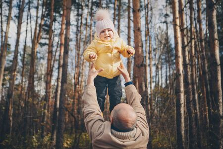a small child with dad in a warm suit walks in the woods. autumn park. The concept of children's fashion, accessories, outdoor walks Stok Fotoğraf - 134409009