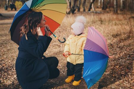 a small child with mother in a warm suit and with a colorful umbrella walks in the woods. autumn park. The concept of children's fashion, accessories, outdoor walks Stok Fotoğraf - 134409010