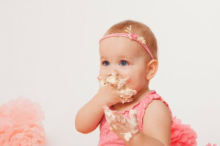 a little girl eats cake with her hands on the bacfground of fireplace. The baby was covered in food. birthday party