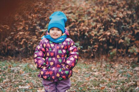 a small child with mother in a warm suit walks in the woods. autumn park. The concept of children's fashion, accessories, outdoor walks Stok Fotoğraf - 134409036