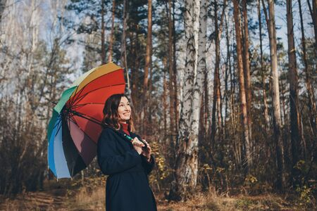 woman funs with a colorful umbrella walks in the woods. autumn park. The concept of fashion, accessories, outdoor walks Stok Fotoğraf