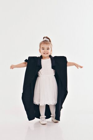 a little girl tries on dad's shirt. Child in big black clothes on white background. Concept of children's games, imitation of adult life, fashion Stok Fotoğraf - 134409059