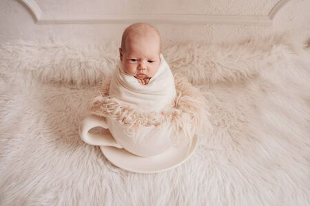 newborn baby in a large tea Cup. concept of childhood, health, IVF, hot drinks, Breakfast
