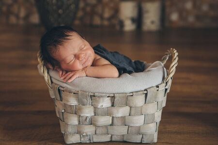 newborn baby wrapped in a blanket sleeping in a basket. concept of childhood, healthcare, IVF. Black and white photo Stok Fotoğraf - 134409078