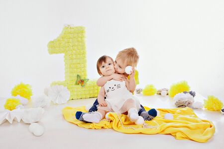 Birthday celebration: girl and boy sitting on the floor among the decoration: numbers 1, artificial flowers and white balls