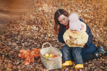 a small child with his mother in a warm suit walking in woods. The woman and girl collect leaves in basket autumn Park. The concept of walking in fresh air, picking fruits: mushrooms, vegetables