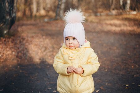 a little girl in a warm hat on his head smiled. the concept of childhood, health, IVF, cold time