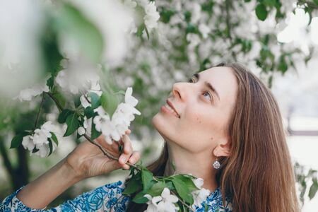 beautiful girl holding flowers. March 8: woman among flowers. the concept of congratulations, women's holidays, natural make up 版權商用圖片