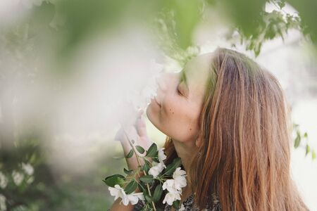 beautiful girl holding flowers. March 8: woman among flowers. the concept of congratulations, women's holidays, natural make up