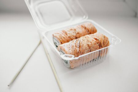Japanese cuisine: rolls in a plastic container. Sushi on white background. Advertising concept of traditional Oriental cuisine, fish food: salmon, tuna, rice