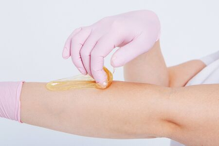 Hands in rubber gloves close-up. doctor puts wax, honey. medic is preparing for depilation. Concept of medicine, medical instruments, health care, beauty industry, hair removal, natural material