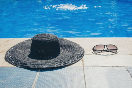 sunglasses and a black hat on a stone slab by the pool close-up. concept of promotional accessories, clothing, beach holiday Фото со стока