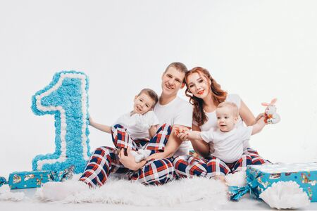 Birthday celebration: family sitting on the floor among the decoration: numbers 1, artificial flowers and gifts. The concept of birthday, holidays. copy space Stok Fotoğraf