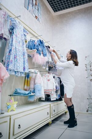 a pregnant woman in a light dress and stockings considers childrens clothes in the shop. Healthy lifestyle concept, IVF fashion for pregnant women, children Stok Fotoğraf