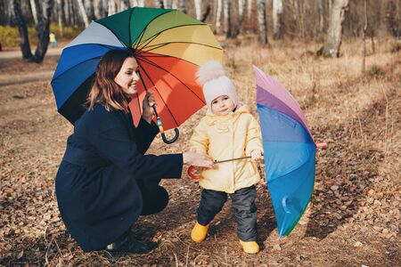 a small child with mother in a warm suit and with a colorful umbrella walks in the woods. autumn park. The concept of childrens fashion, accessories, outdoor walks