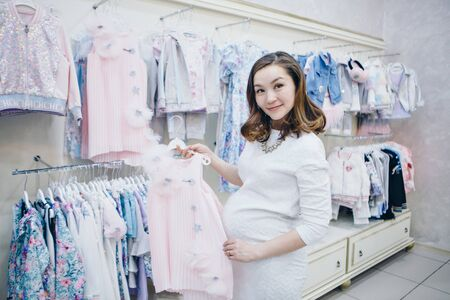 a pregnant woman in a light dress and stockings considers childrens clothes in the shop. Healthy lifestyle concept, IVF fashion for pregnant women, children 스톡 콘텐츠