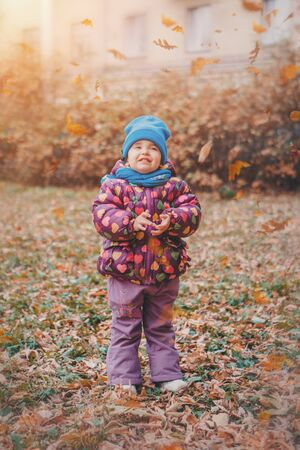 a small child in a warm suit walks in the woods. autumn park. The concept of childrens fashion, accessories, outdoor walks