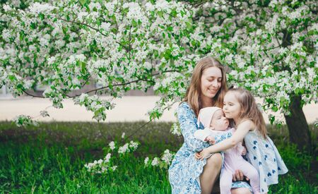 beautiful woman holding children. March 8: women among flowers. the concept of congratulations, womens holidays, natural make up