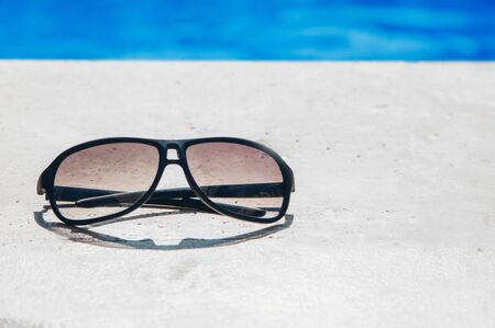 glasses on a stone slab by the pool close-up. the concept of advertising accessories, beach holiday