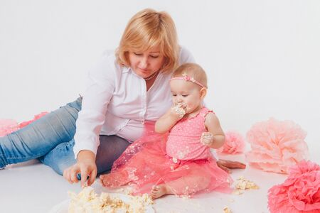 Birthday celebration: little girl eating cake with her hands on white background. child is covered in food. Ruined sweetness. on floor among decoration: numbers 1, artificial flowers and white balls. Copy space Stok Fotoğraf - 135868442