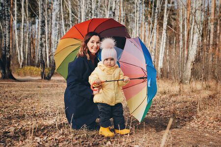 a small child with mother in a warm suit and with a colorful umbrella walks in the woods. autumn park. The concept of children's fashion, accessories, outdoor walks Stok Fotoğraf - 135868444