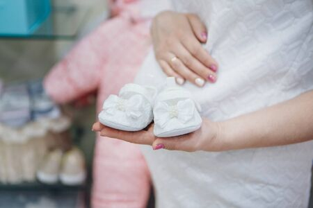 pregnant woman holding baby booties on the belly. fashion for newborns. Children's shoes advertising, IVF Stok Fotoğraf - 135868542