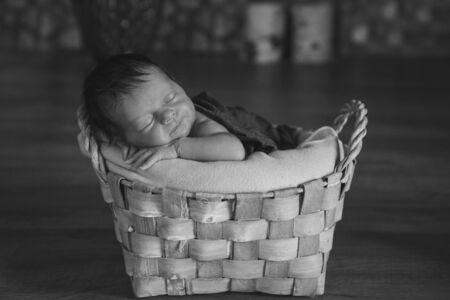 newborn baby wrapped in a blanket sleeping in a basket. concept of childhood, healthcare, IVF. Black and white photo