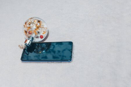 new year's ball and smartphone on a white background. the concept of a lifestyle, IVF, Christmas, new year holidays, toy.solated, business. Copy space Stok Fotoğraf - 135868591