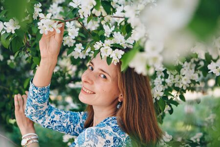 beautiful girl holding flowers. March 8: woman among flowers. the concept of congratulations, women's holidays, natural make up Stok Fotoğraf - 135921566