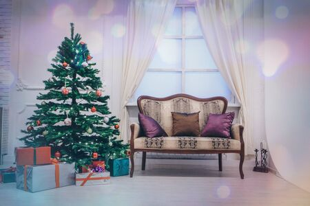 Festive interior: wood and sofa with pillows. gifts under the tree on the background of blurred lights, bokeh. The concept of Christmas and the New year.