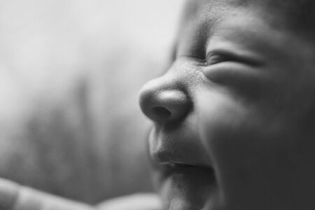 newborn babys face close up: eyes, nose, lips. concept of childhood, health care, IVF, hygiene, ENT