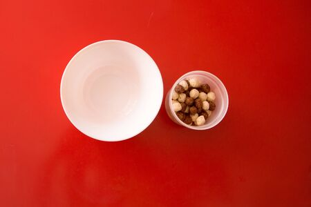 the concept of a delicious and healthy Breakfast, healthy food, advertising chocolate balls with milk. plate, baby food on red background. Copy space