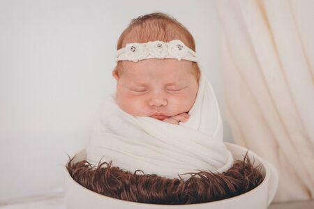 portrait of a sleeping newborn baby in a headband with flower. Stok Fotoğraf