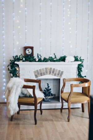Festive interior: armchair, fireplace, Christmas clock and Christmas toys. The concept of Christmas and the New year. Boce as background