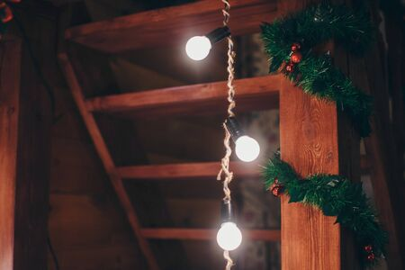 Festive interior: Christmas decorations and light bulbs among the wooden decor. Christmas and New year concept, holiday toys, garland and lighting Stok Fotoğraf - 136079399
