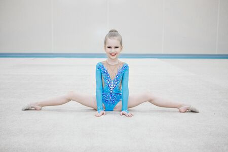 The girl sat down on the twine. classes in the fitness club. the girl is engaged in recreational gymnastics. sports exercises and stretching: athletics