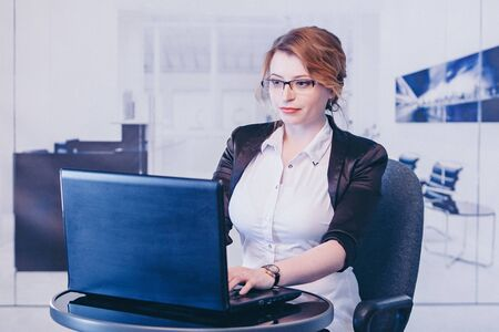 office concept, business plan, fashion-businesswoman in black and white suit working on a laptop. Beautiful woman sitting on chair on the table