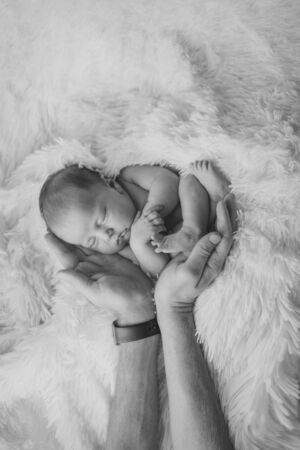 Newborn baby lying on hands of parents. Imitation of baby in womb. beautiful little girl sleeping on her back. manifestation of love. Health care concept, parenthood, children's Day, medicine, IVF